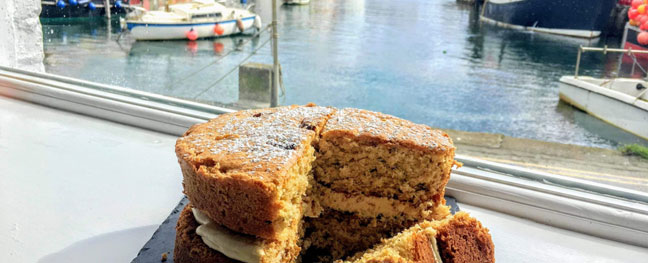 Coffee and walnut cake at Tea on the Quay cafe with a harbour view in Mevagissey Cornwall