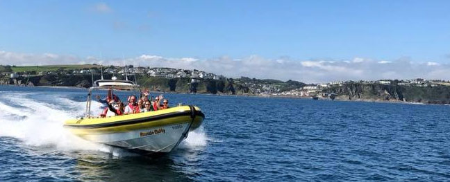 Passengers aboard the Mevagissey Rib Boat waving as they enjoy their ride across the Cornish waters